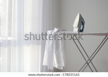 Modern iron and shirt on board Royalty-Free Stock Photo #578035165