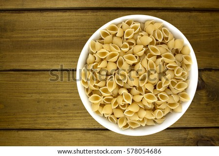 Italian pasta in plate on wooden background #578054686