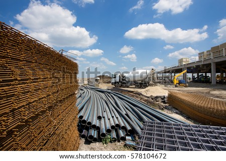 Close up of reinforcement mesh on pile and other construction material and equipment at building site Royalty-Free Stock Photo #578104672