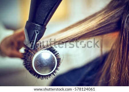 Professional hairdresser drying hair, in studio Royalty-Free Stock Photo #578124061