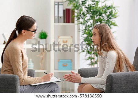 Young female psychologist working with teenager girl in office Royalty-Free Stock Photo #578136550