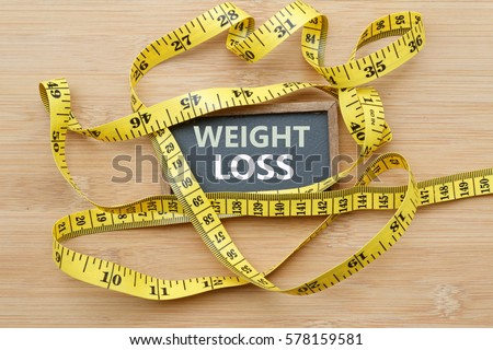Words WEIGHT LOSS written on chalkboard with measuring tape on wooden background. Concept of weight loss, weight management,changing to healthier lifestyle,weight loss health issue and social issue #578159581