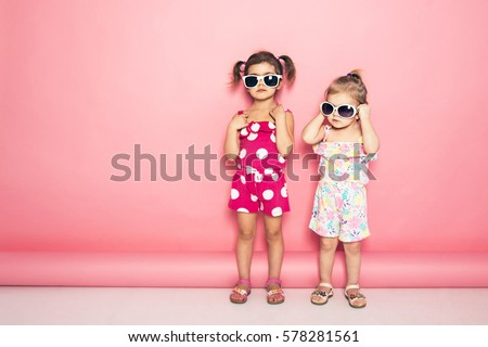Two cute little girls standing in jumpers and sun glasses on the pink background in the studio. Summer, fun, family and vacations concept. Two fashion sisters posing.