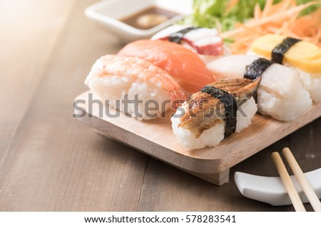 sushi with sauce and wasabi on old brown wood plate, Japanese food #578283541