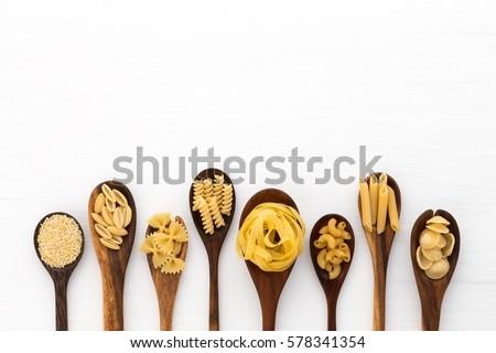 Pasta selection of penne, gnocci, rigatoni, casarecce, fiorelli, pasta Farfalle, pasta A Riso, Orecchiette Pugliesi, Gnocco Sardo and Farfalle in wooden spoons over white background #578341354