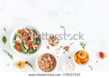 Breakfast with muesli, strawberry salad, fresh fruit, nuts on white background. Healthy food concept. Flat lay, top view. #578357524