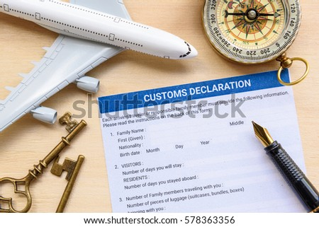 Customs declaration form with a compass, a white model airplane, two brass keys and a fountain pen on a wood table. Passengers must fill and sign this form to declare goods before enter each country.
