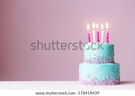 Tiered birthday cake with pink candles