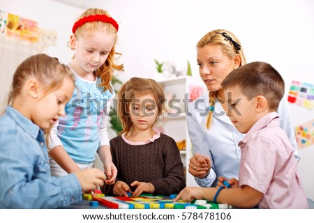 Teacher and children are playing a board game in the classroom #578478106