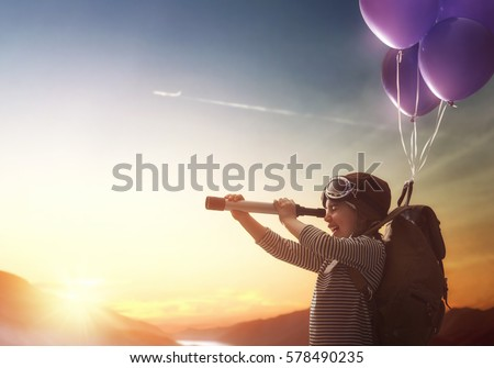 Dreams of travel! Child flying on balloons against the backdrop of a sunset. Royalty-Free Stock Photo #578490235