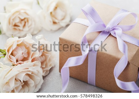Vintage rose flowers and gift box with ribbon on light table. Greeting card for Birthday, Womens or Mothers Day Royalty-Free Stock Photo #578498326