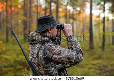 Hunter observing forest with binoculars Royalty-Free Stock Photo #578510659
