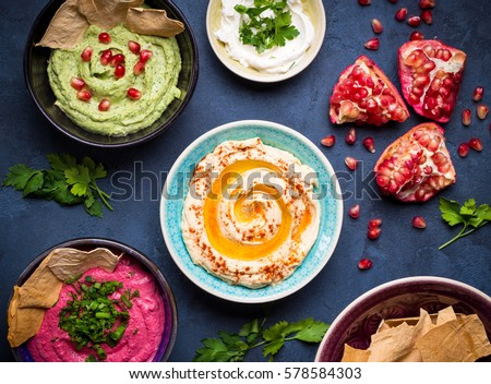 Colorful hummus bowls. Different kinds of dips. Traditional hummus, herbs hummus, beetroot hummus, spread. Assorted meze and dips with crispy pita. Meze and snacks concept. Middle eastern snacks set #578584303