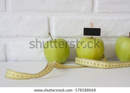 Studio shot of whole green healthy fresh apple with tape measure against white brick wall background. Healthy lifestyle. Diet or weight losing concept. Sport style of life. Scandinavian organic food. #578588068