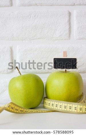Studio shot of whole green healthy fresh apple with tape measure against white brick wall background. Healthy lifestyle. Diet or weight losing concept. Sport style of life. Scandinavian organic food. #578588095