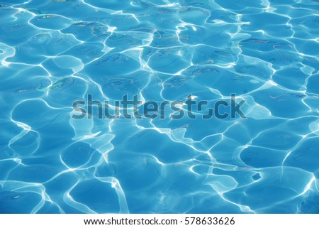 Blue romantic rippling water surface with sun glare. The glare from the sun on the waves #578633626