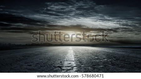 Beautiful, rural, dirt road between fields late at night on the background of beautiful sunset clouds. #578680471