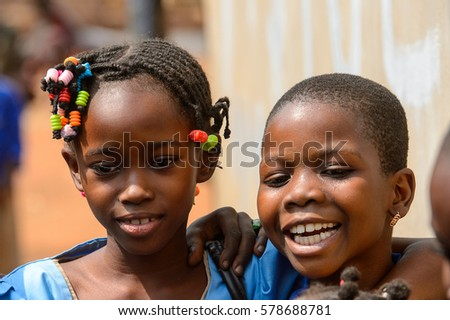 PIRA, BENIN - JAN 12, 2017: Unidentified Beninese children in school uniform smile. Benin kids suffer of poverty due to the bad economy. #578688781
