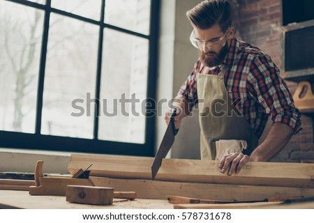 young stylish cabinet-maker with  glasses and hairstyle. Strong  handsome craftsman holding saw and wood blank at workplace. #578731678