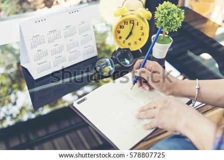 2020 Calendar event planner timetable agenda plan on organize schedule event. Wedding planner agenda organizing timetable by organizer schedule. Woman hands note on calendar desk. Calendar event plans