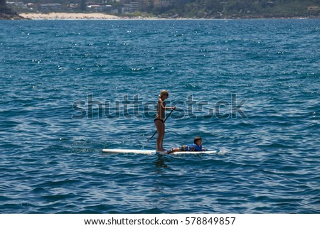 SYDNEY - FEB 05 2017: Mother and kid playing surf together on summer at Mainly beach, Sydney, Australia. #578849857