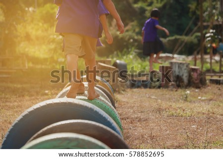 Kids playing in the playground. Running on tires.selective focus #578852695