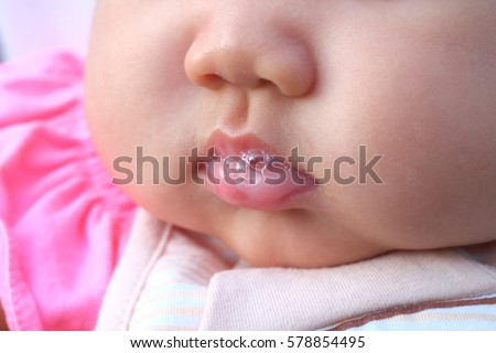 close up baby infant is playing saliva Royalty-Free Stock Photo #578854495