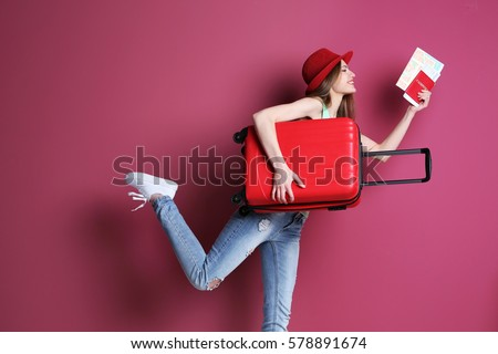 Woman traveler with suitcase on color background Royalty-Free Stock Photo #578891674