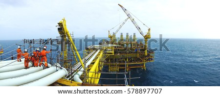 Oil and gas industries. Panorama view of offshore scaffolders standing on the pipeline and new oil and gas platform installed in the middle of the sea with cloudy sky background. Royalty-Free Stock Photo #578897707