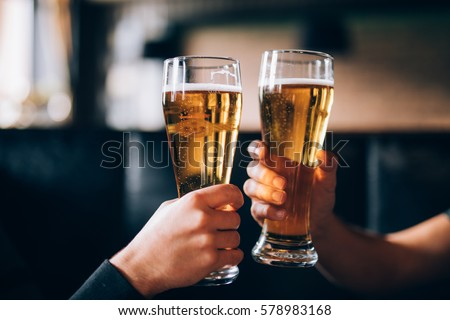 Cheers. Close-up of two men in shirts toasting with beer at the bar counter Royalty-Free Stock Photo #578983168