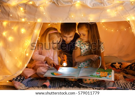 Cute little children reading book in hovel at home #579011779