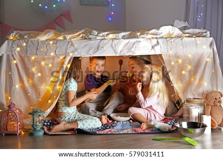 Young woman and cute children playing in hovel at home #579031411