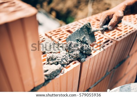 Industrial worker using trowel and tools for building exterior walls with bricks and mortar #579055936