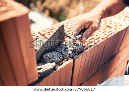 industrial details - Construction bricklayer worker building walls with bricks, mortar and putty knife #579056017