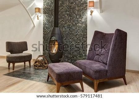 Stylish interior of living room with fireplace where fire is burning and basket with firewood near. Two armchair and little table. Room in gray, violet and white colors. #579117481