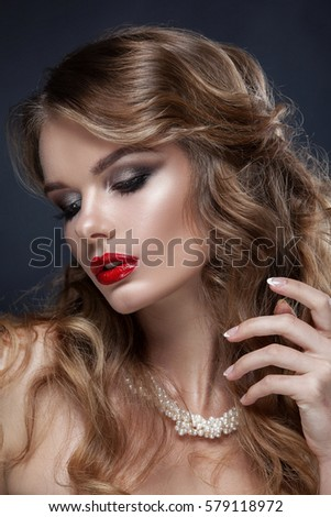 Beautiful portrait of a young girl, professional make-up with red lipstick. On the neck jewelry made of pearls, shot against a dark background. Clean skin, beauty. #579118972
