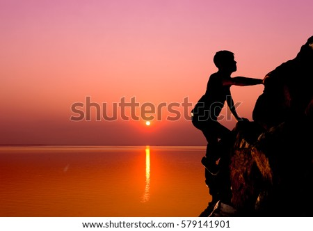 Mountain climber on sun set at sea background.motivation concept