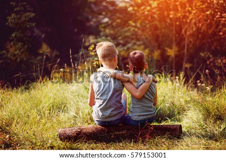 Two little boys friends hug each other in summer sunny day. Brother love. Concept friendship. Back view. Royalty-Free Stock Photo #579153001