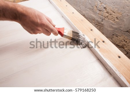 Man's hand painting wooden table with brush #579168250