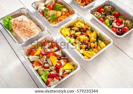 Healthy food background. Take away of natural organic meals in foil boxes. Fitness nutrition, meat, fresh salads, fruits and vegetables. Restaurant dishes delivery #579233344