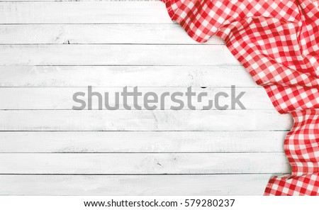 White old vintage wooden table with a red checkered tablecloth.