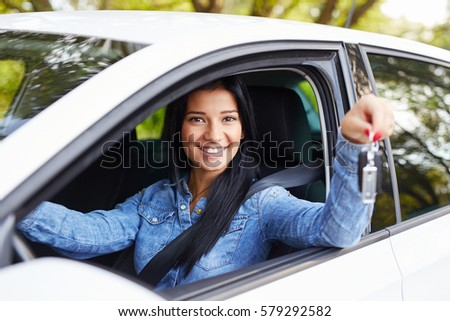 Happy woman sitting in the car and holding key #579292582