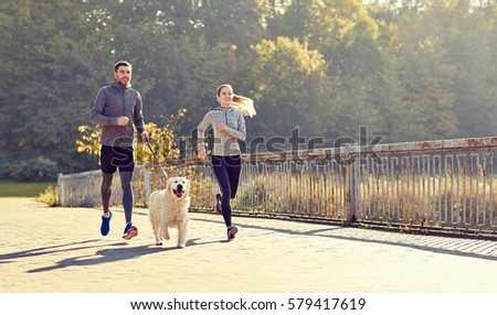 fitness, sport, people and lifestyle concept - happy couple with dog running outdoors #579417619