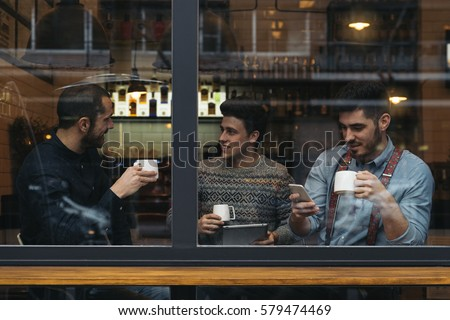Friends drinking coffee and chatting in cafe. Royalty-Free Stock Photo #579474469