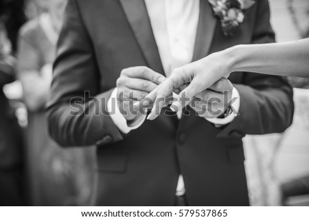 The groom wears a ring for bride. black and white photo. #579537865