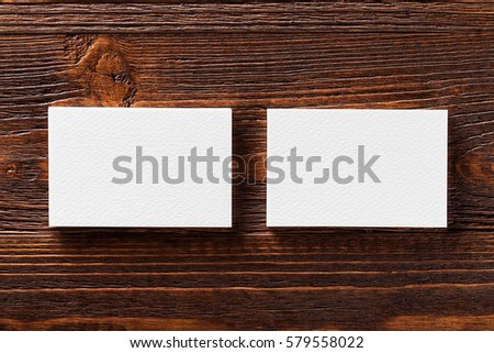 Closeup mockup of two white horizontal business cards at brown wooden table background.