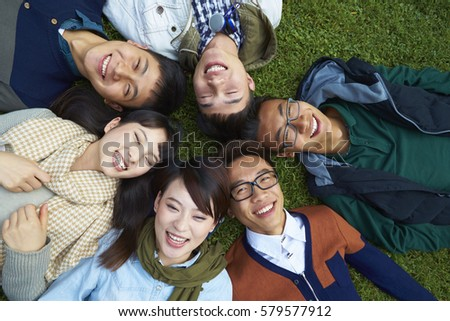 Group of Happy Chinese College Students Lying on Lawn Lokking up to the Camera smile #579577912