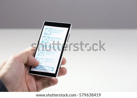 Designer hand holding smart phone with paper sketch for mobile responsive website #579638419