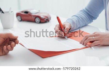 Woman signing a car insurance policy, the agent is holding the document