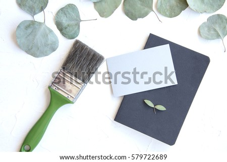 Business card mock up with green brush, eucalyptus leaves on concrete background #579722689